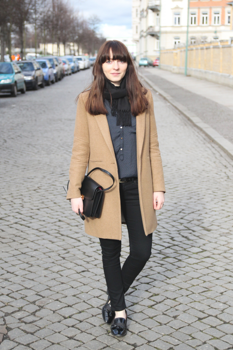 camel coat, black jeans and blue blouse