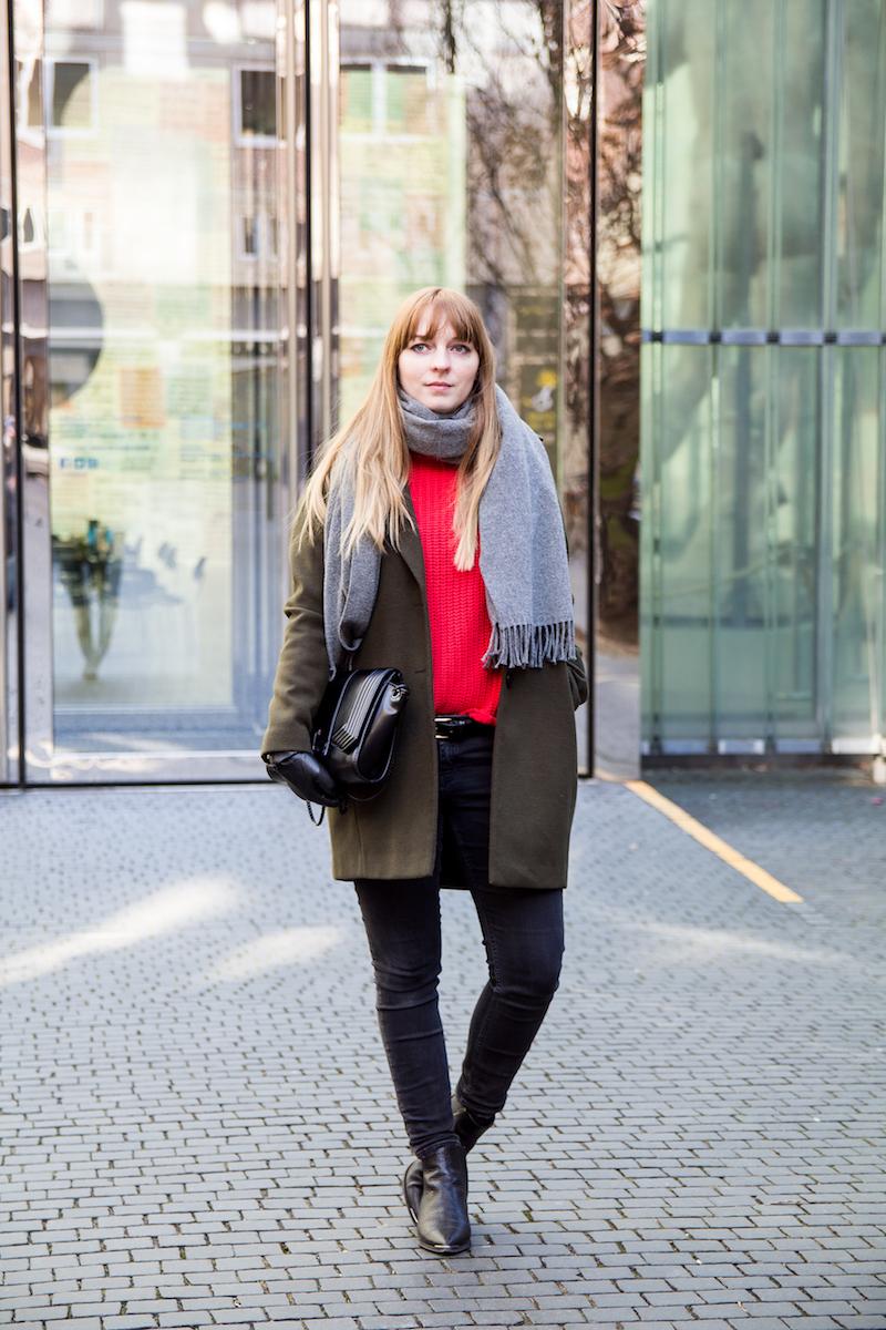 Outfitkombination mit rotem Strickpullover und khakifarbenen Mantel